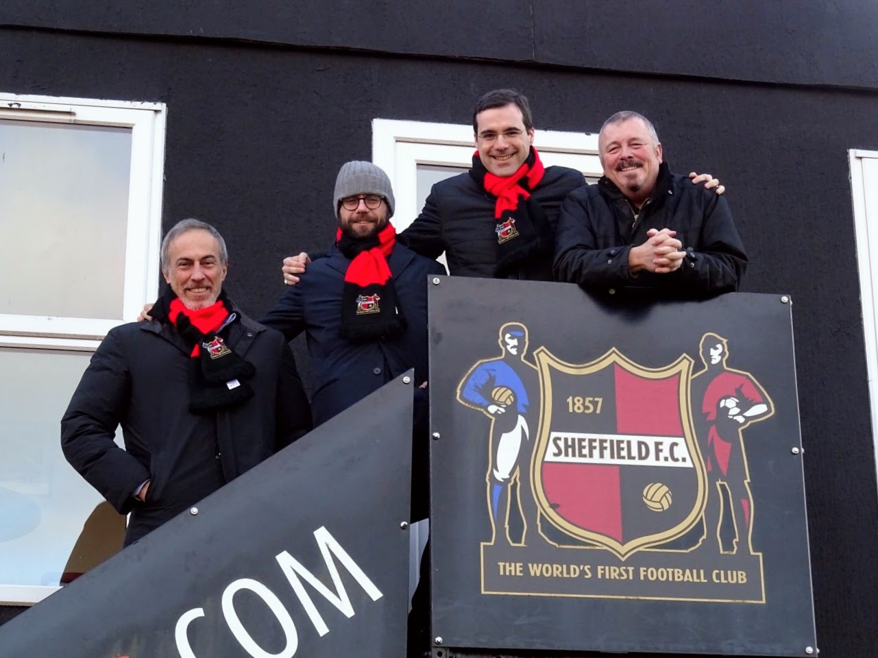 Members of Sheffield FC and LSG Sports stand on steps outside the Club's office